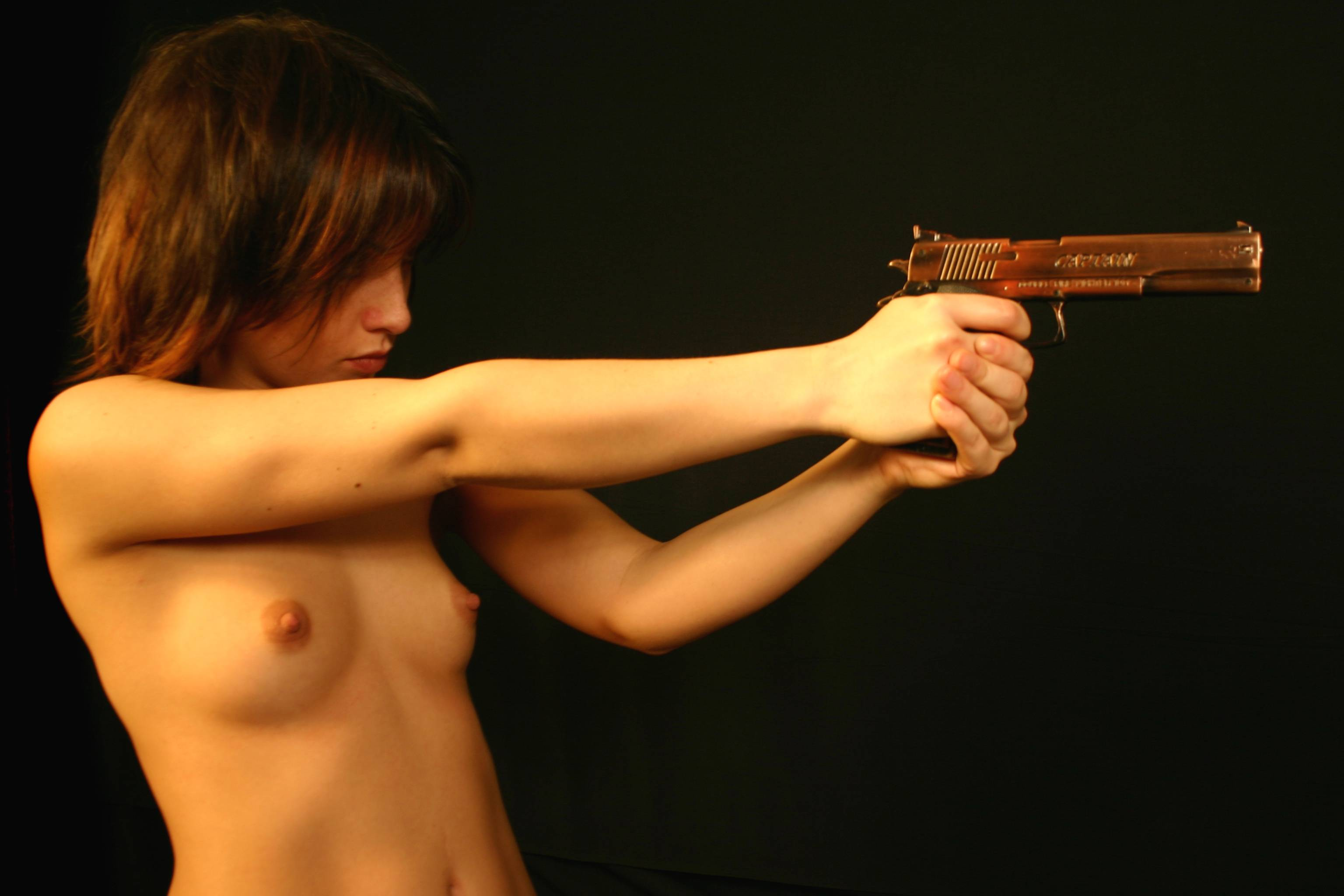 Hot topless babe with gun
