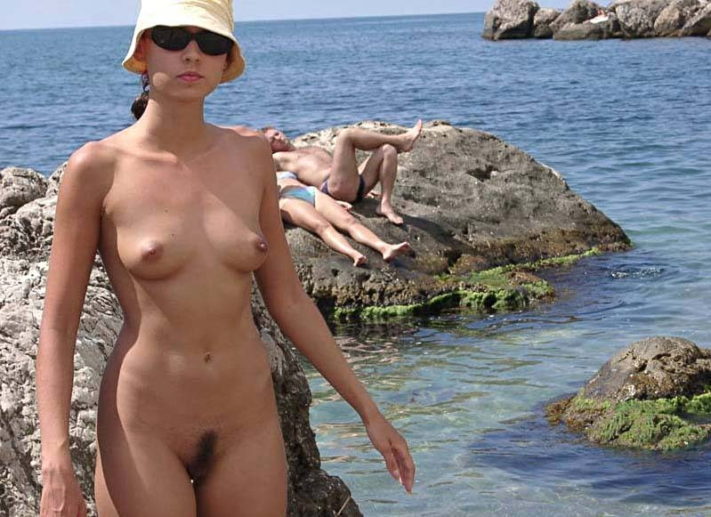 Amateur nude chick reveal her furry muff near the ocean