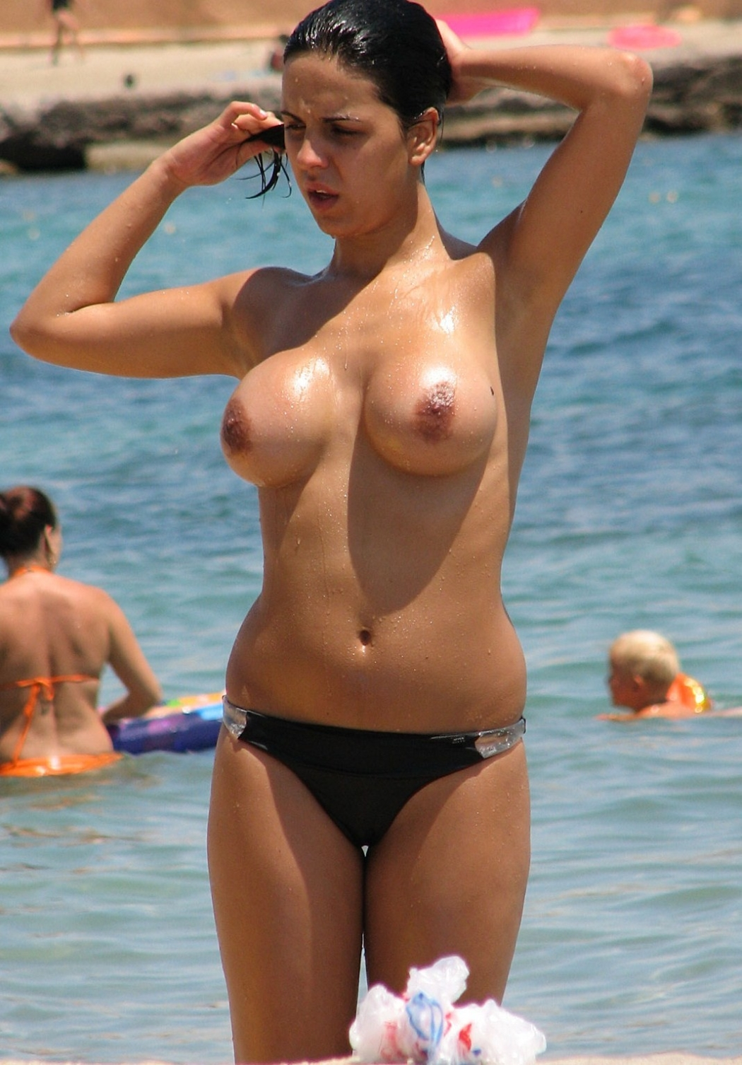 Curvy brunette swimming topless
