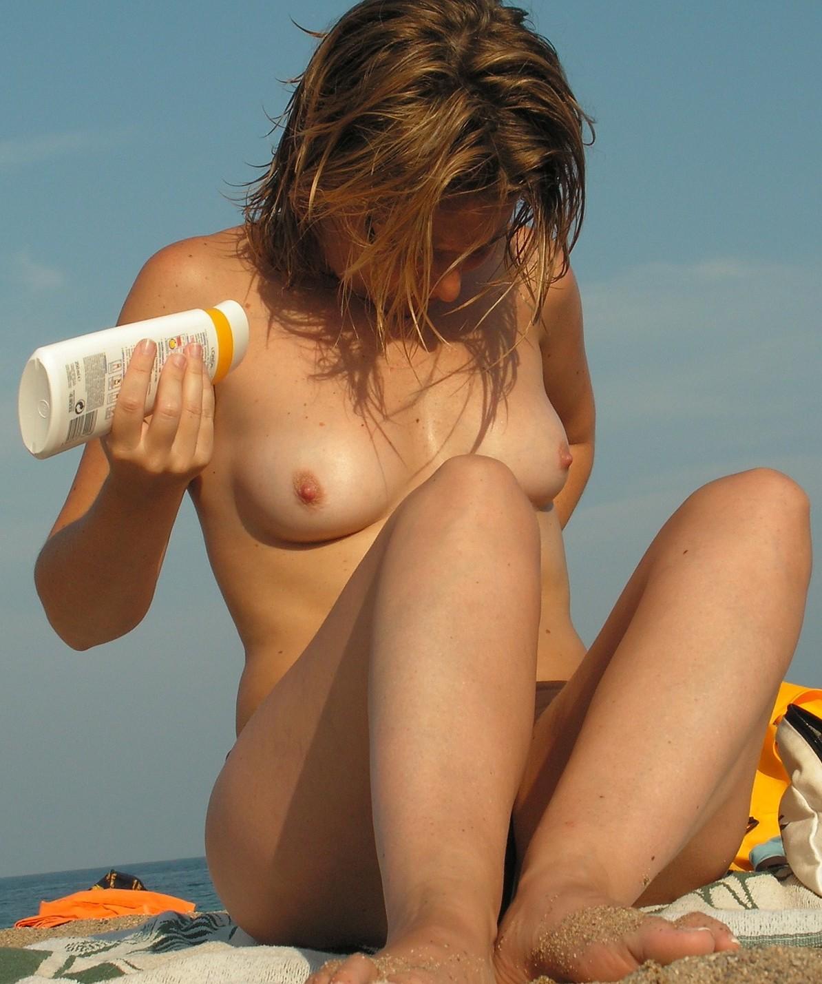 Nude hottie rubbing on lotion in the beach sun