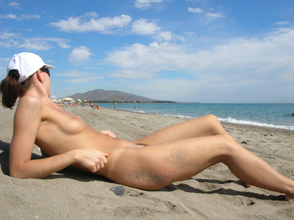 Resting her naked body on the warm sand