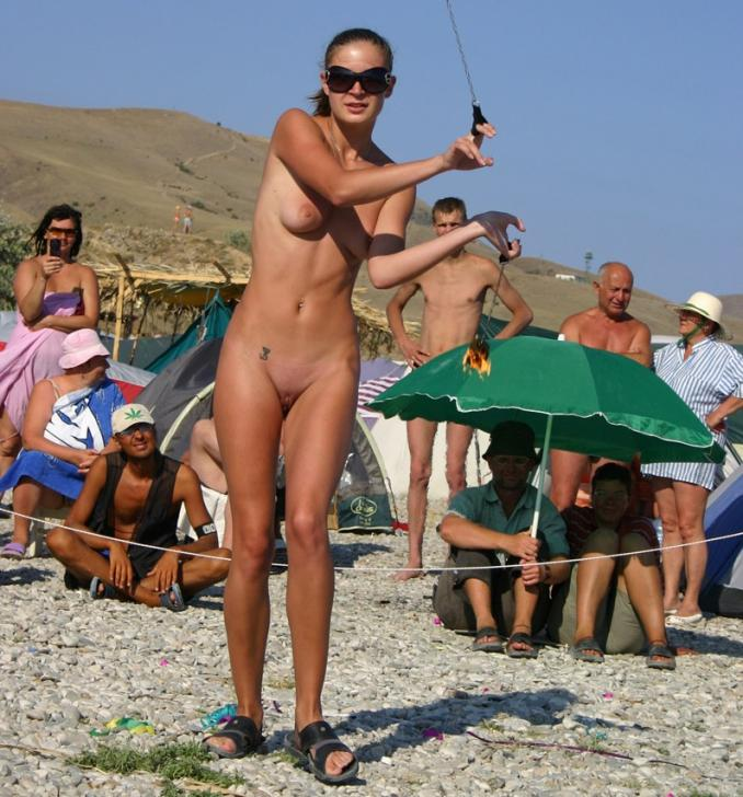 Tanned woman shows off shaved pussy for crowd