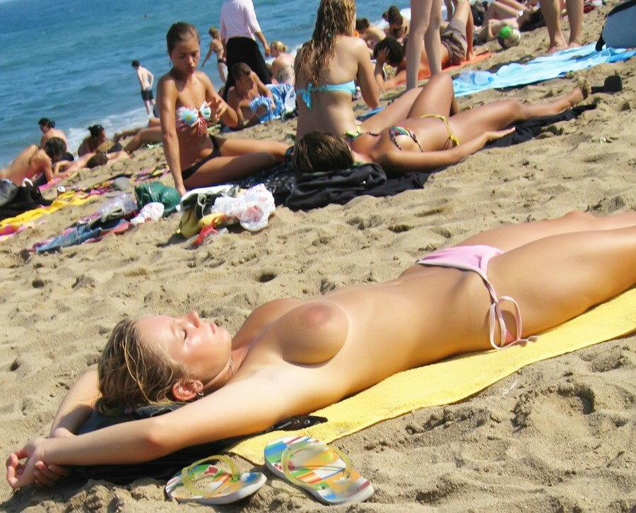 Topless hottie tanning her round tits